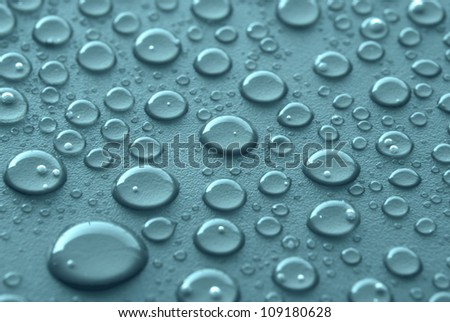 Shiny water drops sprayed on textured blue surface. - stock photo