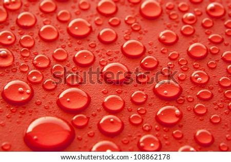 Shiny water drops sprayed on textured red surface. - stock photo