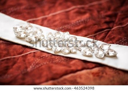 Shiny wedding belt decorated with jewelry on red sofa. Marriage concept