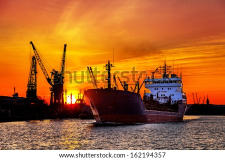 Ship and cranes at sunset in port of Gdansk, Poland.