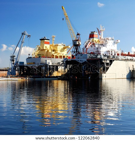 ship are being fixed and painted at the shipyard docks - stock photo