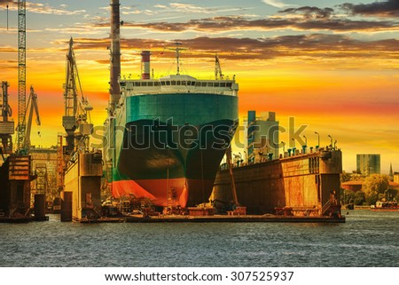 Ship being repaired in dry dock at sunset in Gdansk, Poland.