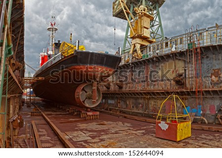 Ship for repairs in large floating dry dock. - stock photo