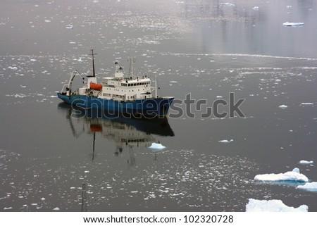 Ship in Antarctic waters beetween snow - stock photo