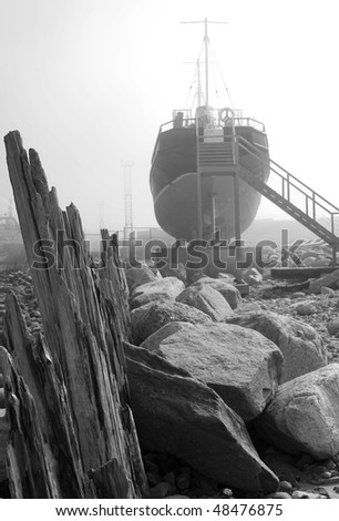 Ship in fog on ground. Black and white photo.