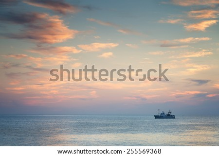 Ship in the sea at sunset - stock photo