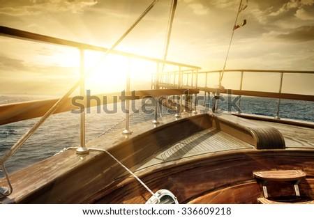 Ship in the sea in sun beams - stock photo
