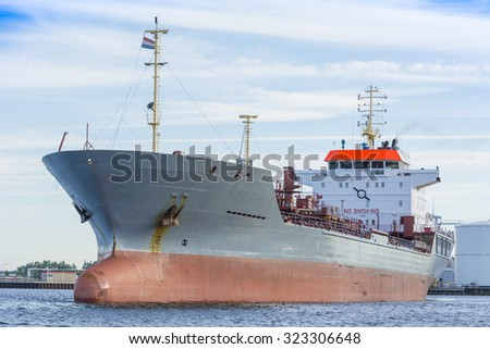 Ship is sailing in the port of Amsterdam. The tanker is finished with cargo operations and is heading to sea. - stock photo
