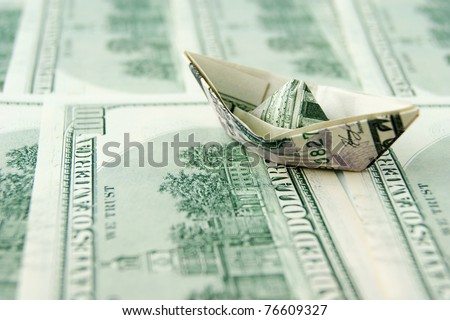 Ship made of dollar note on dollar notes background - stock photo