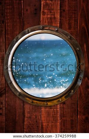 Ship porthole on wooden wall - stock photo