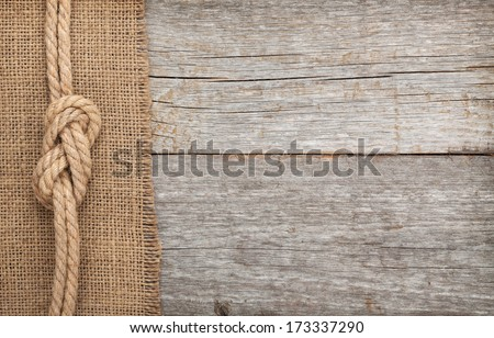 Ship rope on old wood and burlap texture background with copy space - stock photo