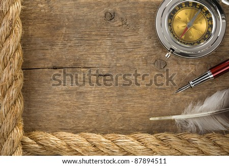ship ropes and compass at old wooden background