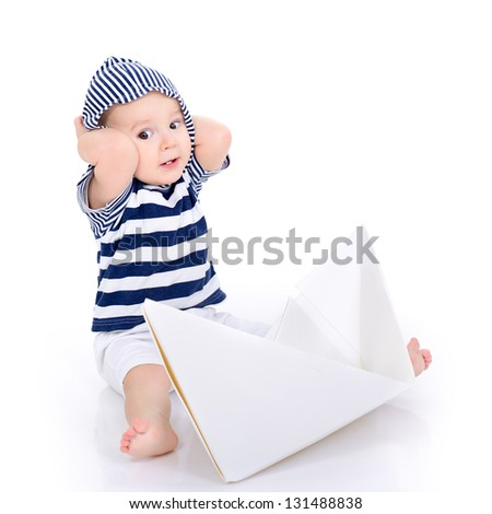 ship's boy. cute baby boy sitting in striped vest with ship of paper - sailor in future, over white background - stock photo