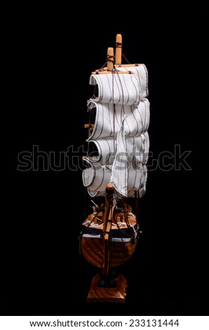 Ship Sailboat Wooden Model Figurine on a Black Background