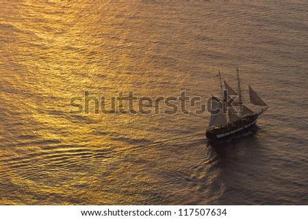 Ship sailing at sunset - stock photo