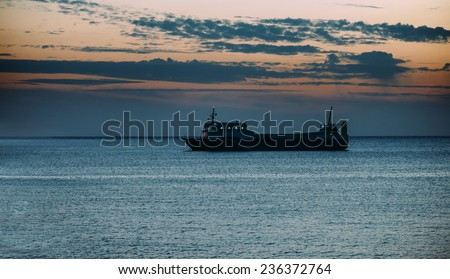 Ship sailing in the blue sea at beautiful sunset. Space for text in lower part of image