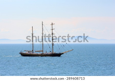 Ship sailing in the sea on mountain background