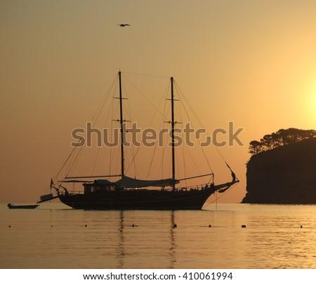 Ship silhouette and island on sunrise - stock photo