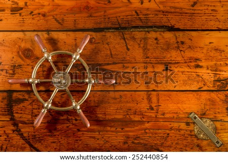Ship Wheel on Textured Wood - Brass ship's wheel on textured wooden hatch cover.  Vibrant textures and lighting with copy space on right. - stock photo