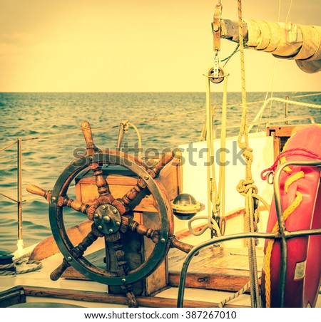 Ship wheel on the old yacht. Nautical equipment in vintage style. Steering wheel on the old sailboat. Sea voyage of the sailing vessel. Travel at sail boat with wooden helm. - stock photo