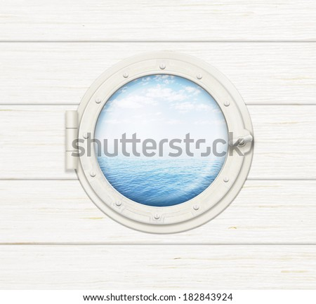ship window or porthole on wooden wall with sea or ocean visible through it - stock photo