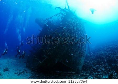 Ship wreck Gainnis D and divers. Red Sea. - stock photo