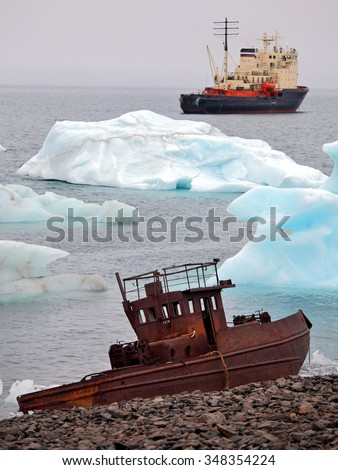 Ship wreck on Arctic coast with icebergs and icebreaker on background - stock photo