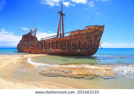 Ship wreck surrounded by sea waves on sunny Selinitsa beach, Gytheio, Greece - stock photo