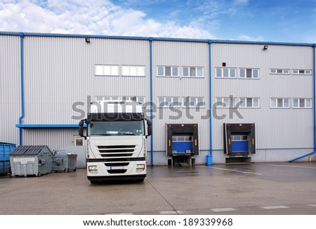 Shipping cargo truck at warehouse building - stock photo