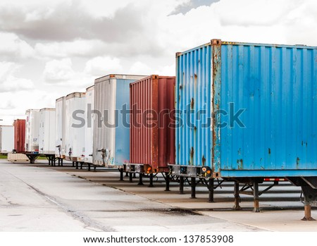 Shipping containers and semi truck trailers waiting in parking lot at huge loading dock - stock photo