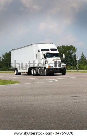 shipping truck driving down road on blue sky - stock photo