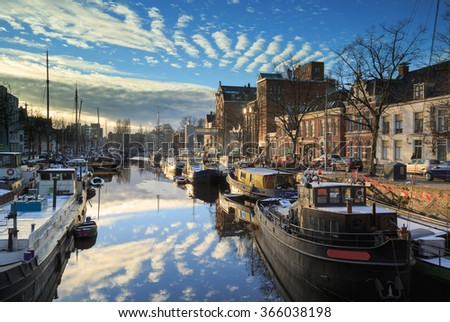 Ships and boats in a canal in Groningen, Noorderhaven, on a cold day in winter. - stock photo