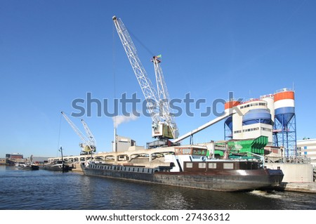 Ships in the harbor, with cranes unloading sand and a cement factory painted in the colors of the Dutch flag