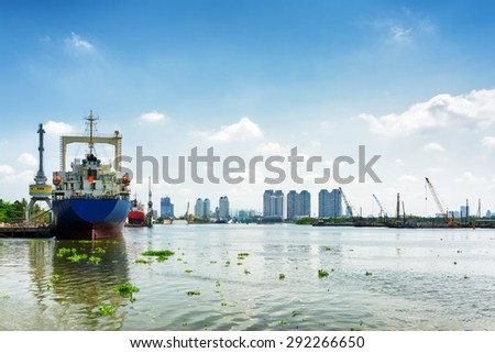 Ships on the Saigon River in territory of Ba Son Shipyard on blue sky background in Ho Chi Minh city, Vietnam. Modern buildings are visible in background. Ho Chi Minh is a popular tourist destination. - stock photo