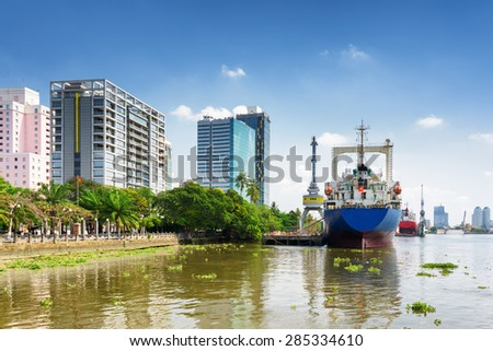 Ships on the Saigon River in territory of Ba Son Shipyard on blue sky background. Modern buildings on waterfront in Ho Chi Minh city, Vietnam. Ho Chi Minh is a popular tourist destination of Asia. - stock photo