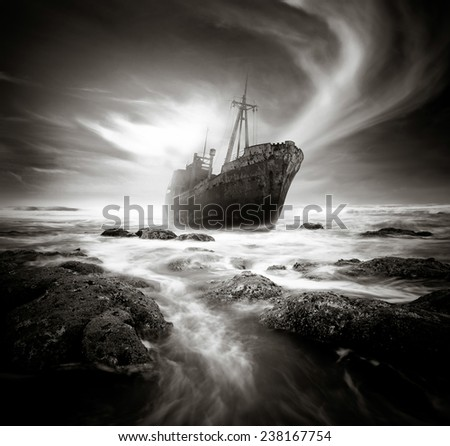 Shipwreck along a rough and rocky coastline. - stock photo