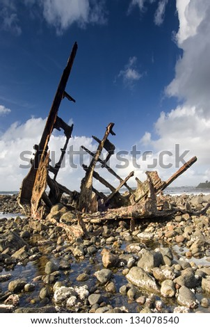 Shipwreck on rocky beach - stock photo
