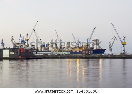 Shipyard with dock ship and cranes in the port of hamburg - stock photo