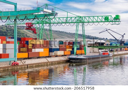 Shipyard with stacked cargo containers and cranes - stock photo