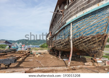 Shipyard Wreck with old wood. Waiting for repair - stock photo