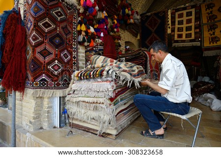 SHIRAZ - APRIL 14: Traditional iranian carpets in a market (Vakil Bazaar) in Shiraz, Iran on April 14, 2015. Vakil Bazaar is the most important tourist attraction in Shiraz, Iran. - stock photo