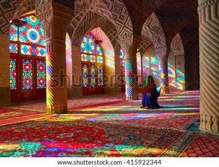 SHIRAZ, IRAN - March 01, 2016: Young Muslim woman praying in Nasir Al-Mulk Mosque (Pink Mosque), Iran, Shiraz - stock photo