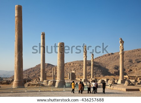 SHIRAZ, IRAN - SEPTEMBER 17, 2014: Group of tourists visiting ruins of Apadana Palace in Persepolis city. construction of this city began at 518 BC under rule of King Darius from Achaemenid dynasty. - stock photo