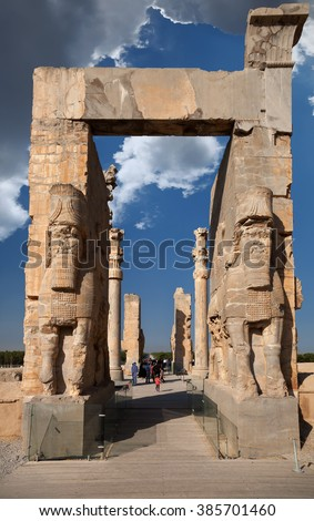 SHIRAZ, IRAN SEPTEMBER 17, 2014: People passing through Gate of All Nations in Persepolis ancient city. construction of this city began at 518 BC under rule of King Darius from Achaemenid dynasty. - stock photo