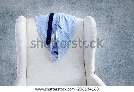 shirt and tie hanging on a chair - stock photo