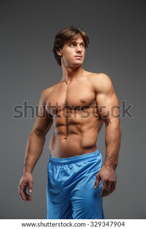 Shirtles muscular man in blue shorts showing his muscles over grey background. - stock photo