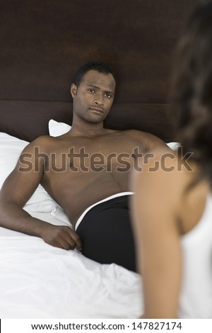 Shirtless African American man looking at cropped woman in bed - stock photo