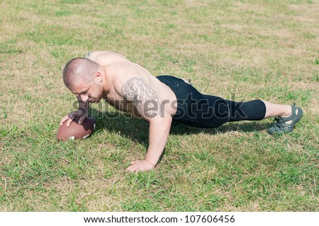 Shirtless american football player doing push-ups with ball on the playfield