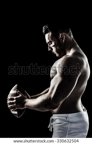 Shirtless American football player with ball against black
