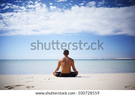Shirtless Asian meditating by the ocean in Western Australia